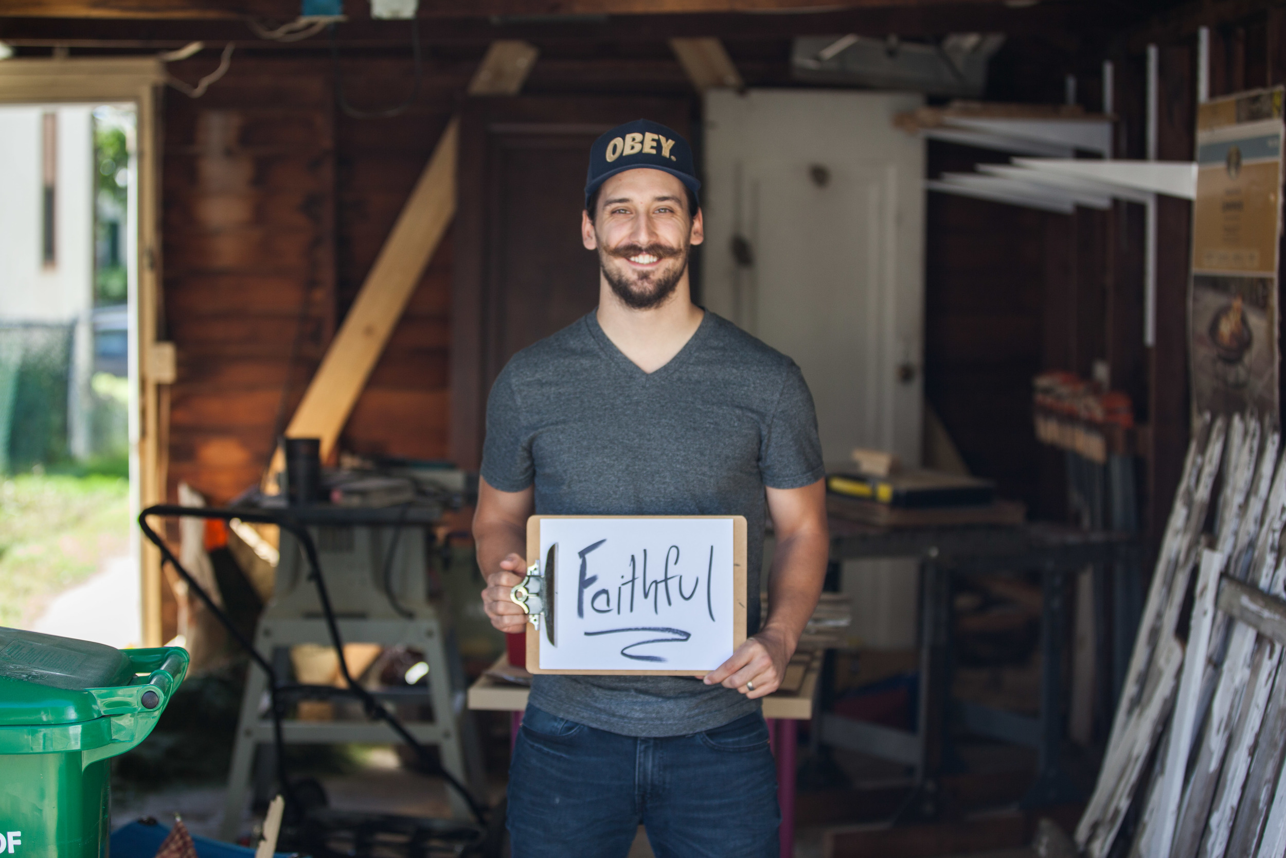 Man holding a sign saying faithful while standing in his garage.