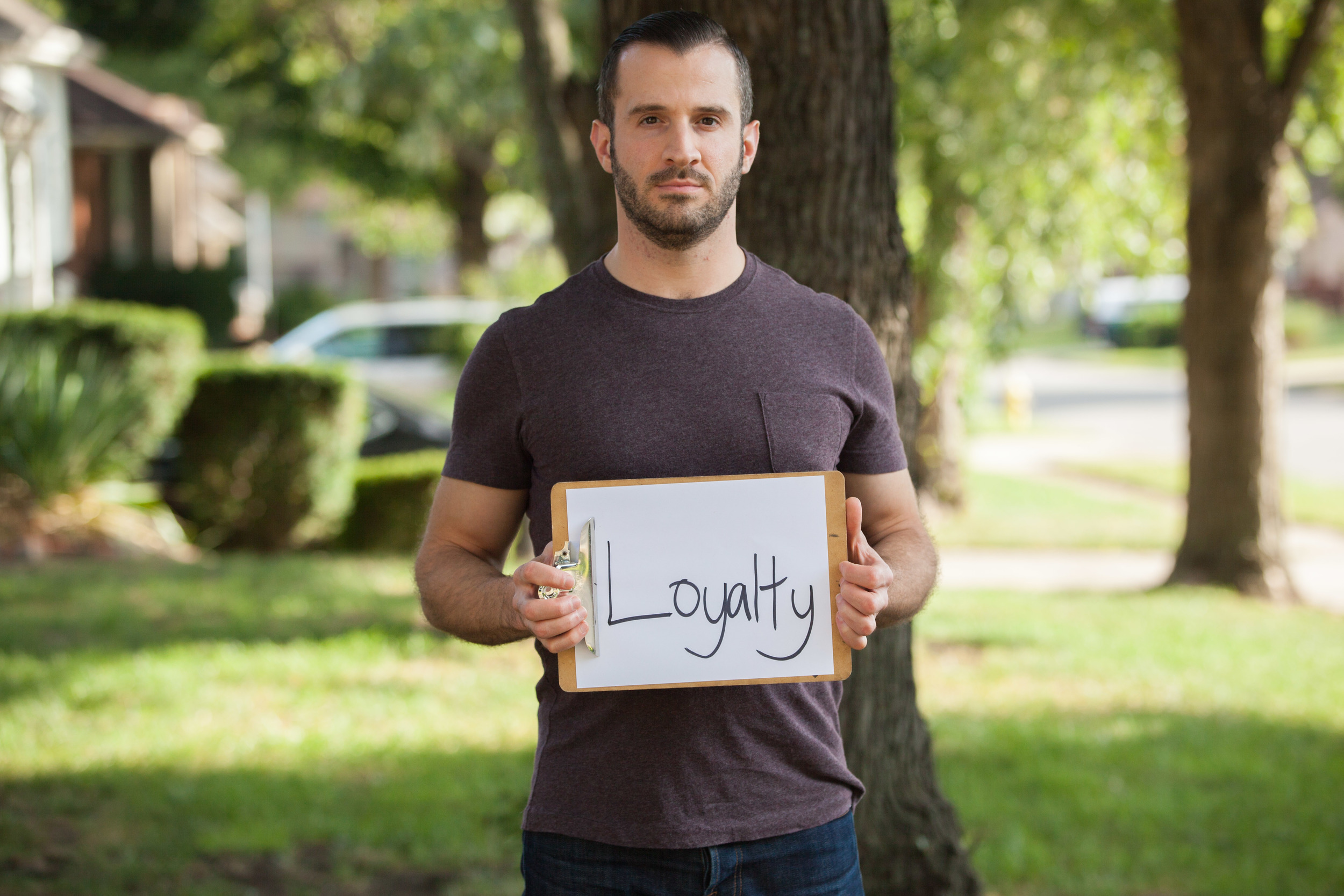 Man standing outside holding a sign that says loyalty.