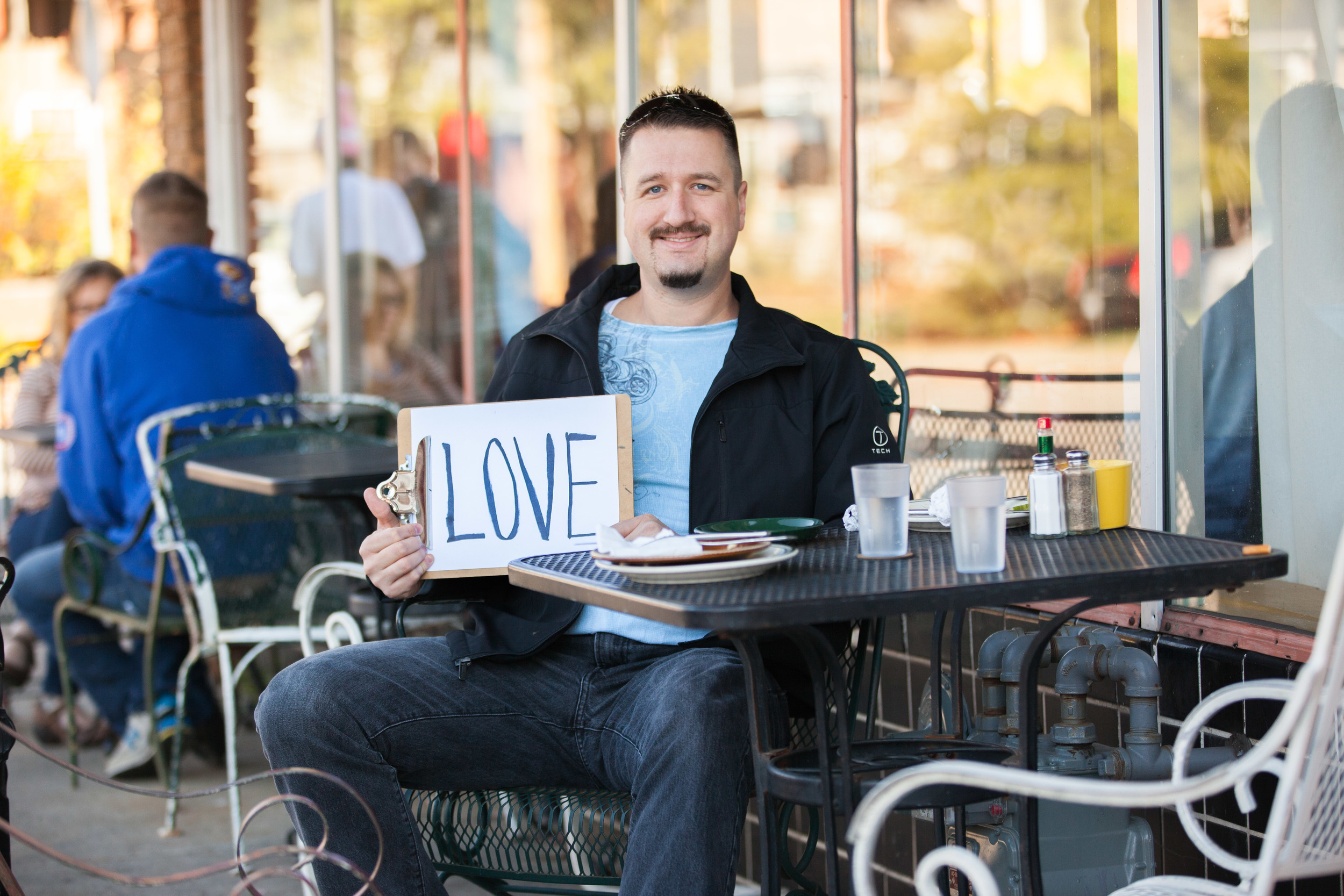 Man sitting at a cafe holding a sign that says love.
