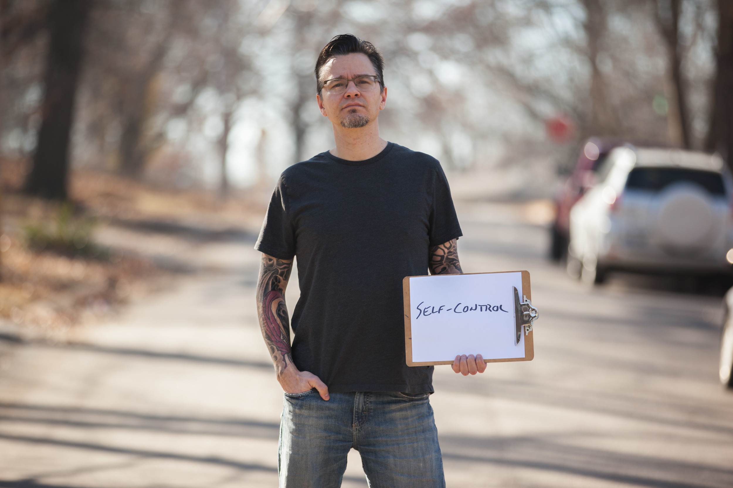 Man holding a sign that says self-control.