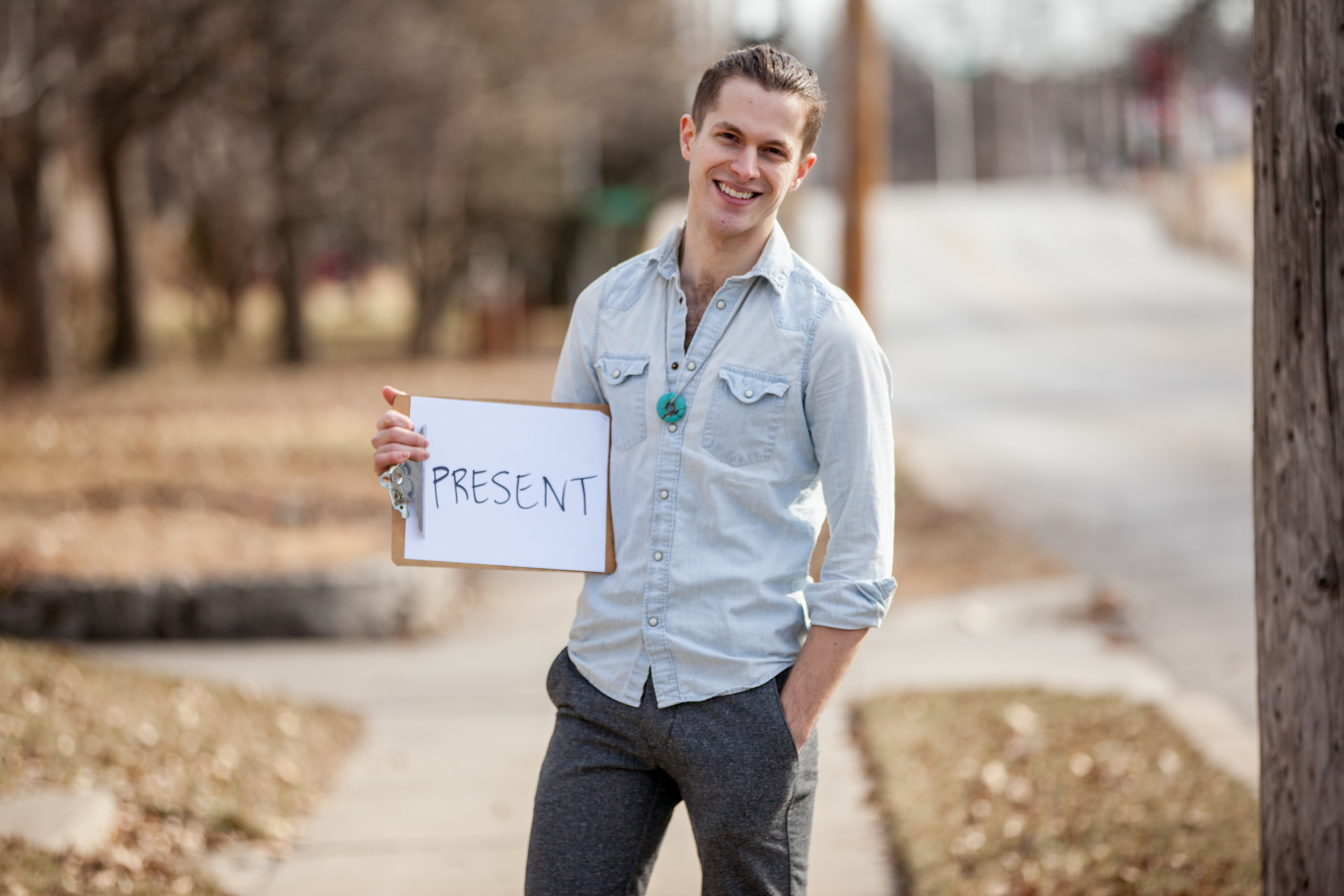 Man holding a sign that says present.