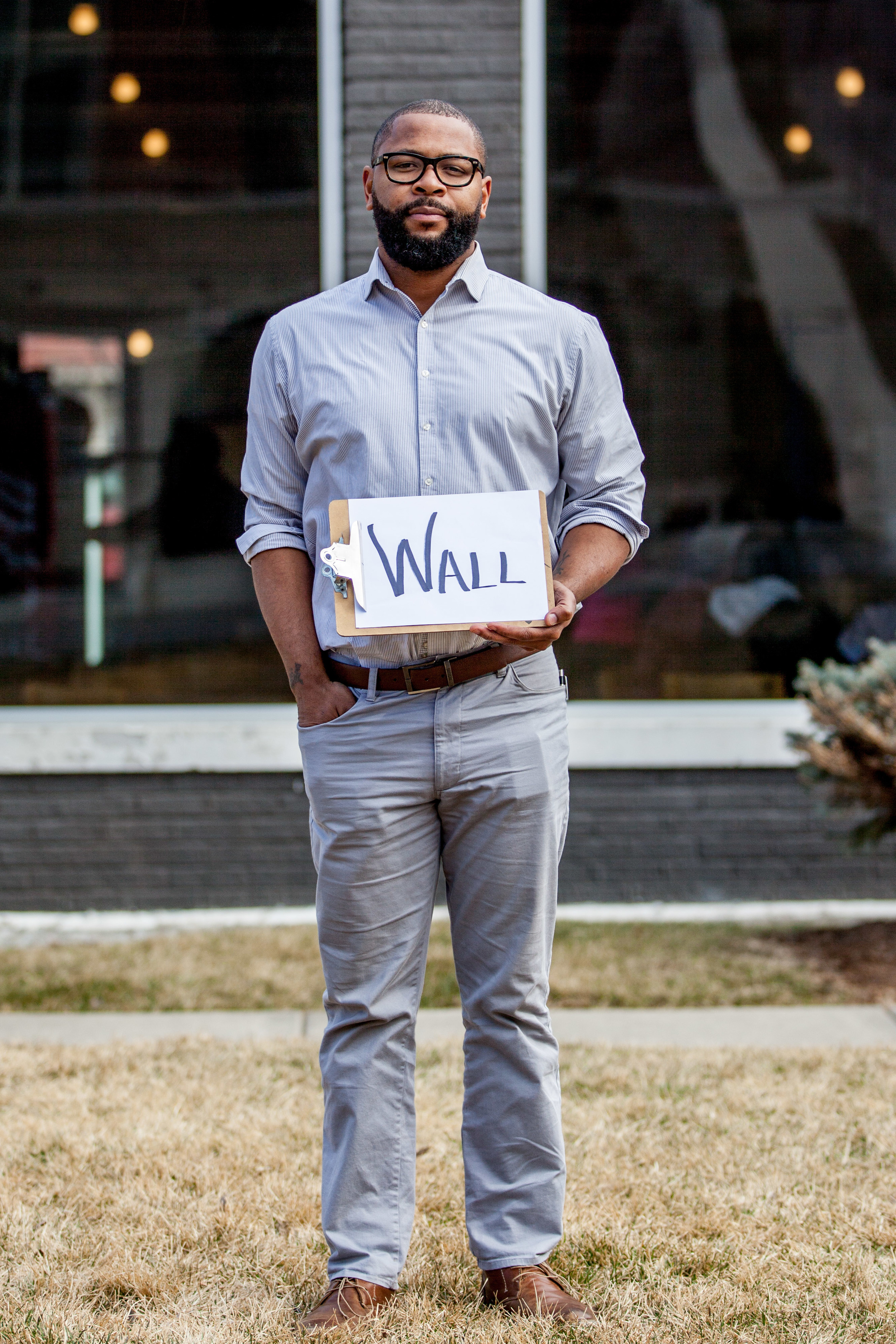 Man standing outside holding a sign that says wall.