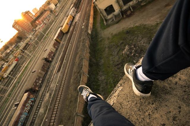 Man sitting overlooking traintracks and the horizon.