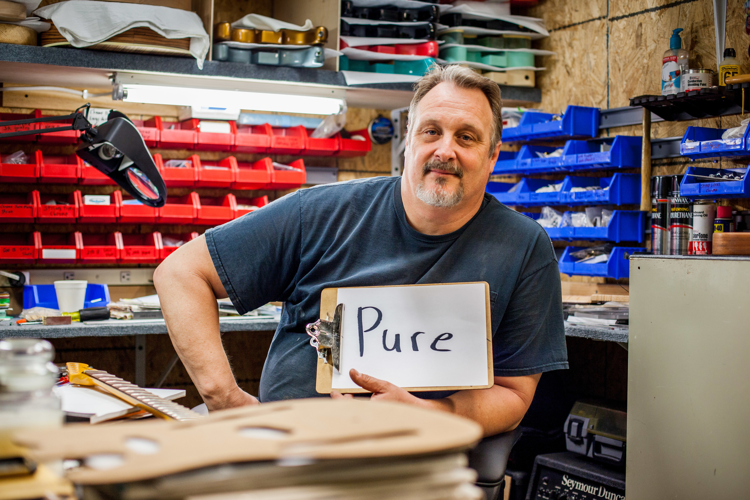 Man holding a sign saying pure while sitting in his work shop.