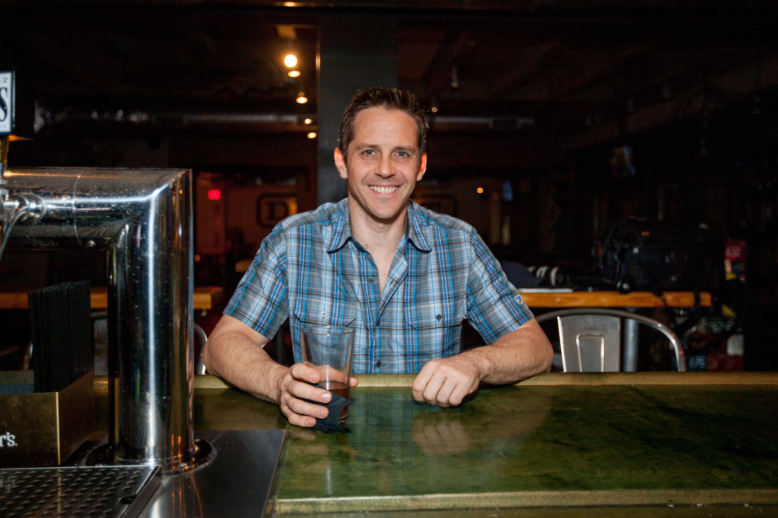 Man sitting at a bar with a beer glass in his hand.