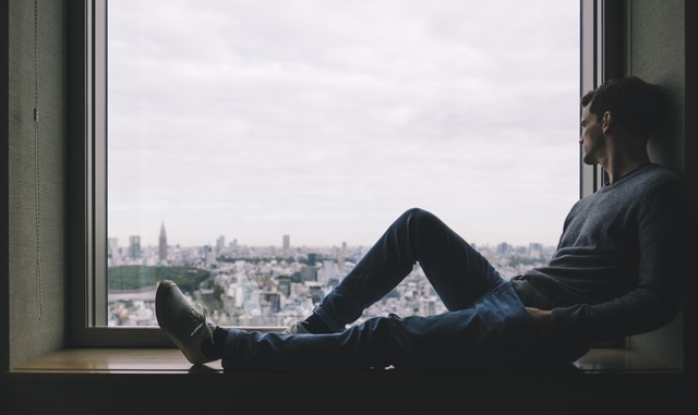 Man sitting in a window sill looking over a city scape.