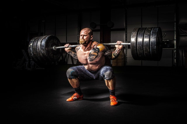 Man doing a squat lifting a large amount of weight.