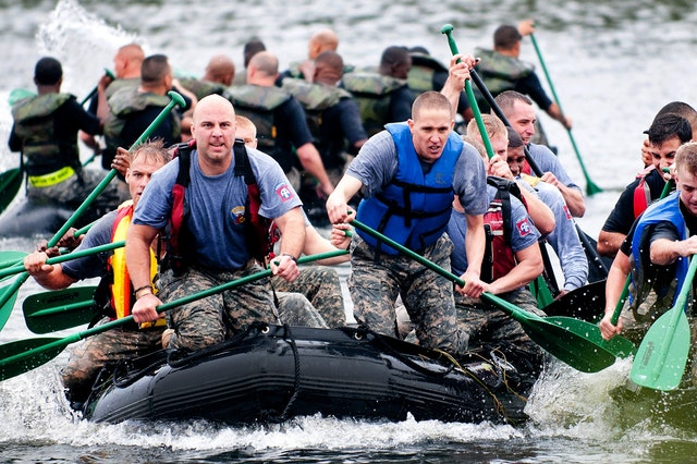 Men in a white water raft wearing life jackets and camoflauge clothing.