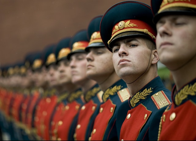A row of military men standing in formation and one man looking at the camera.