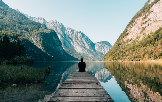 Man sitting on the end of a dock overlooking a valley that has a lake in it.
