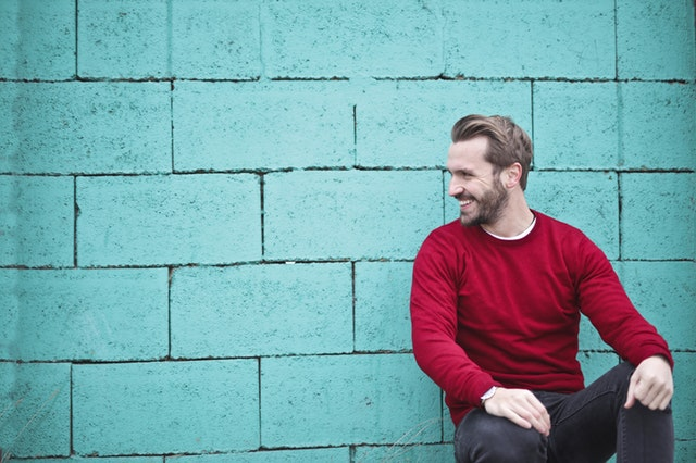 Masculine man smiling while leaning against a brick wall.