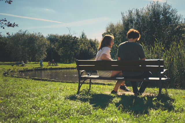 Young man and young woman sitting on a bench at a park.
