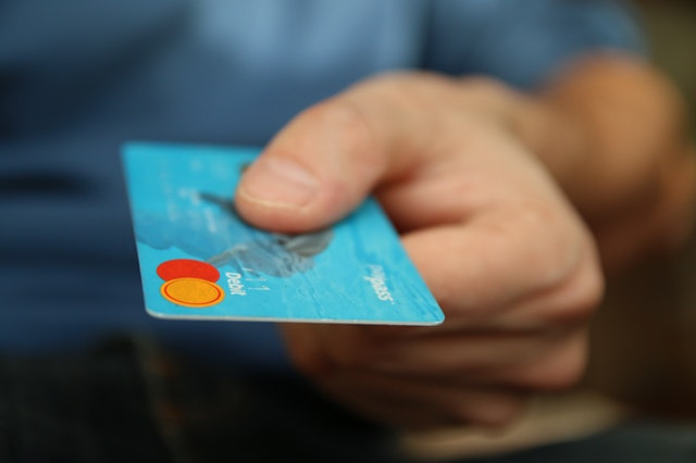 A man holding his debit card in one hand.