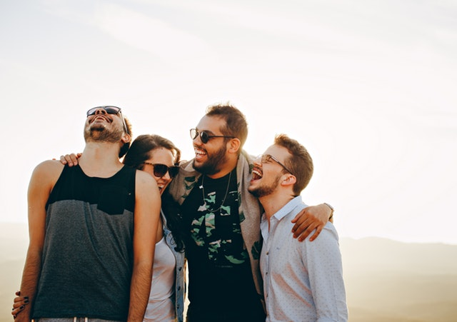 A group of men and a woman hugging each other laughing.