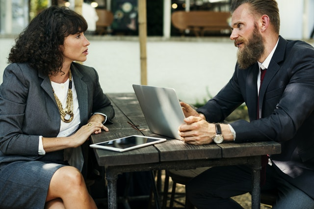 Business man and woman talking at a table outside.