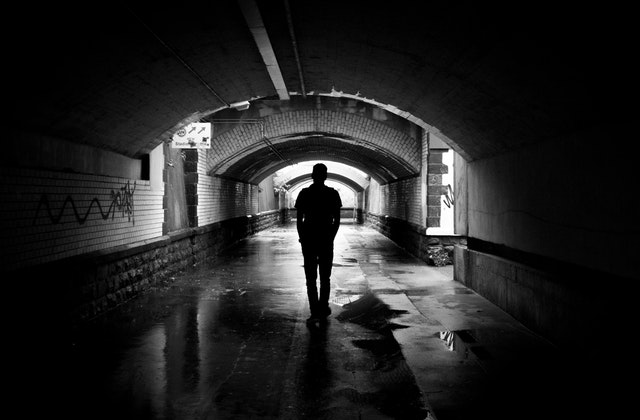 Man walking down a tunnel with the light shining in front of him,