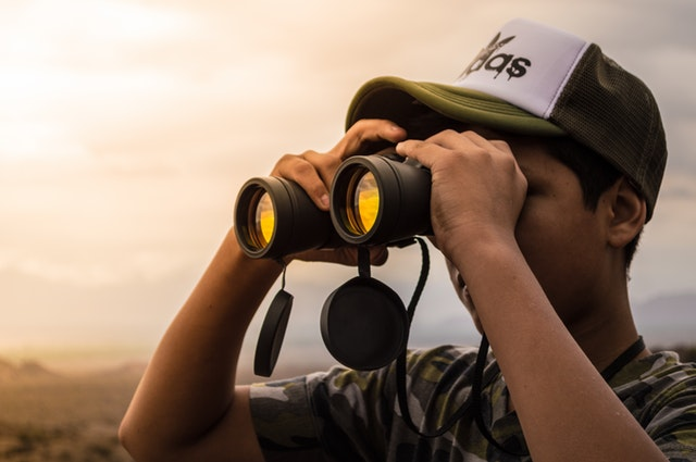 A confident man holding a pair of binoculars up to his eyes.