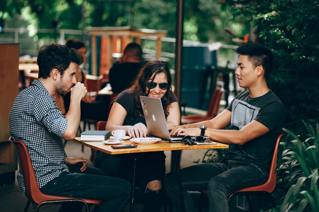 Two confident men talking with a woman at a coffee shop.