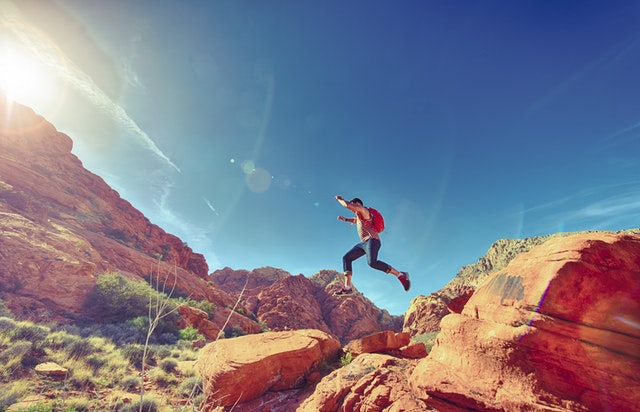 Man of action jumping in the wilderness.