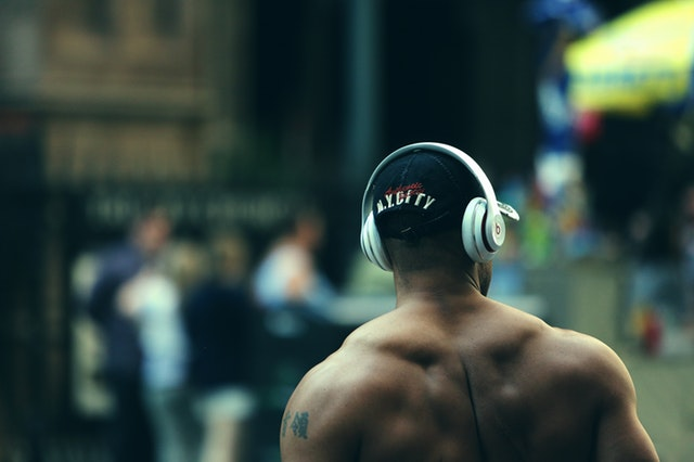 Masculine man practicing being present while listening to music.