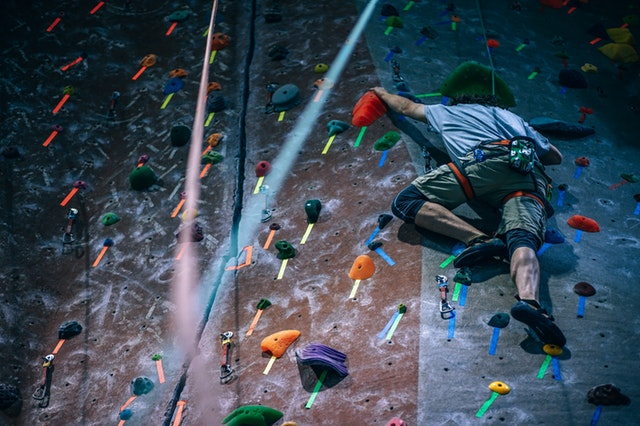 Male friendship man climbing a wall.