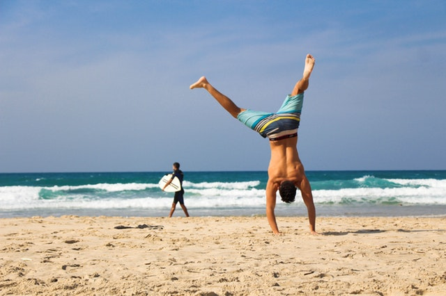 Male friendship. Guy on beach doing a cartwheel. Man walking with surfboard.