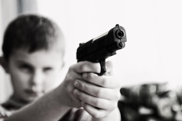 Masculinity, mass shootings, practical ways for men to respond. Boy holding a gun.