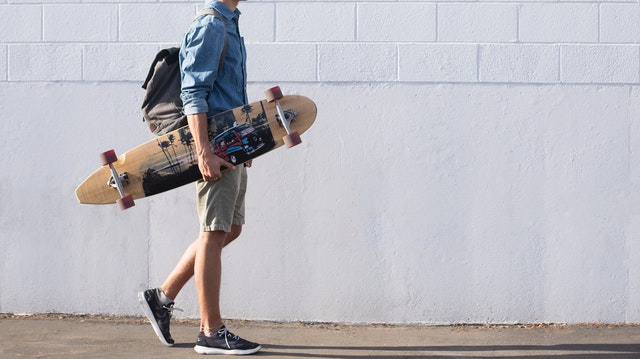 man walking with a longboard thinking about mental health