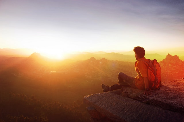 a man sitting on a ledge of a mountain enjoying the view