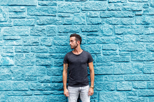 Man standing by a wall look over his right shoulder.