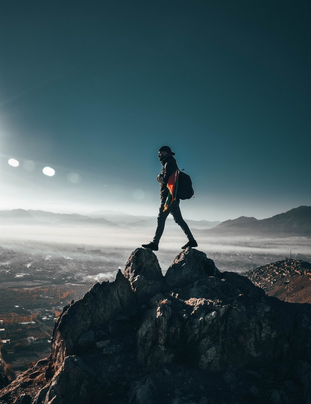 dude posing on some rocks on a mountain side