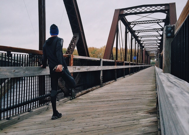 man warming up to go for a run on a bridge