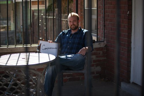 a guy sitting in a yard with Compassion sign in his hands