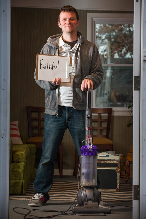 man standing in the living room with a vacuum cleaner, holding Faithful sign