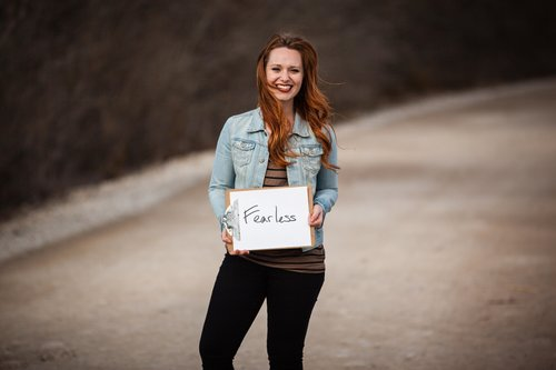 redhead standing on a road and holding a sign