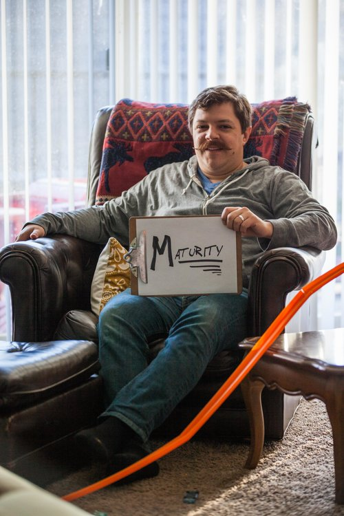 a man sitting in a chair with Maturity sign in his hands