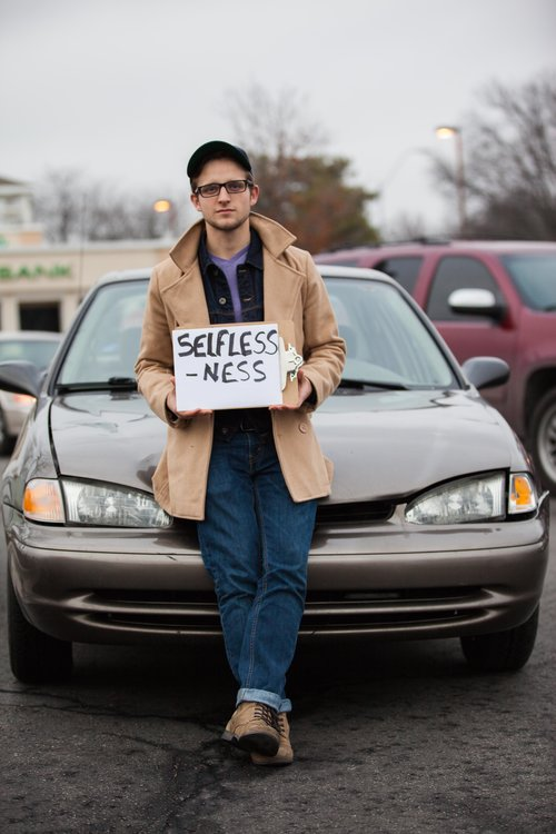man with a cap leaning against a car, holding a sign