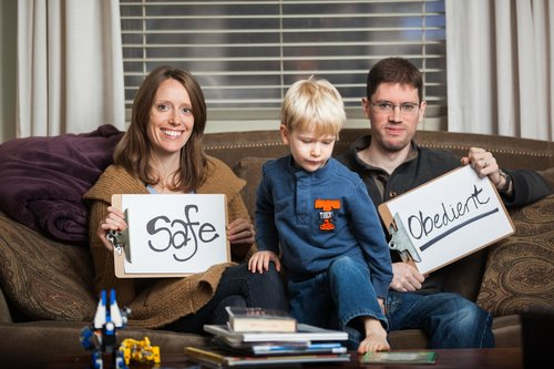 couple sitting on the couch with their son, both holding signs