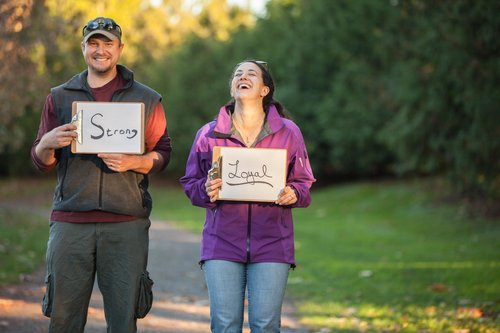 couple standing in a park, laughing and holding signs
