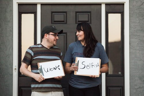 couple standing in front of the door, looking at each other and holding signs
