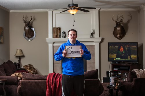man standing in the living room, holding a sign