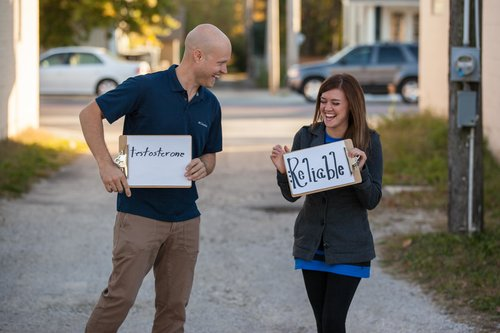 couple standing on a sidewalk, laughing and holding signs