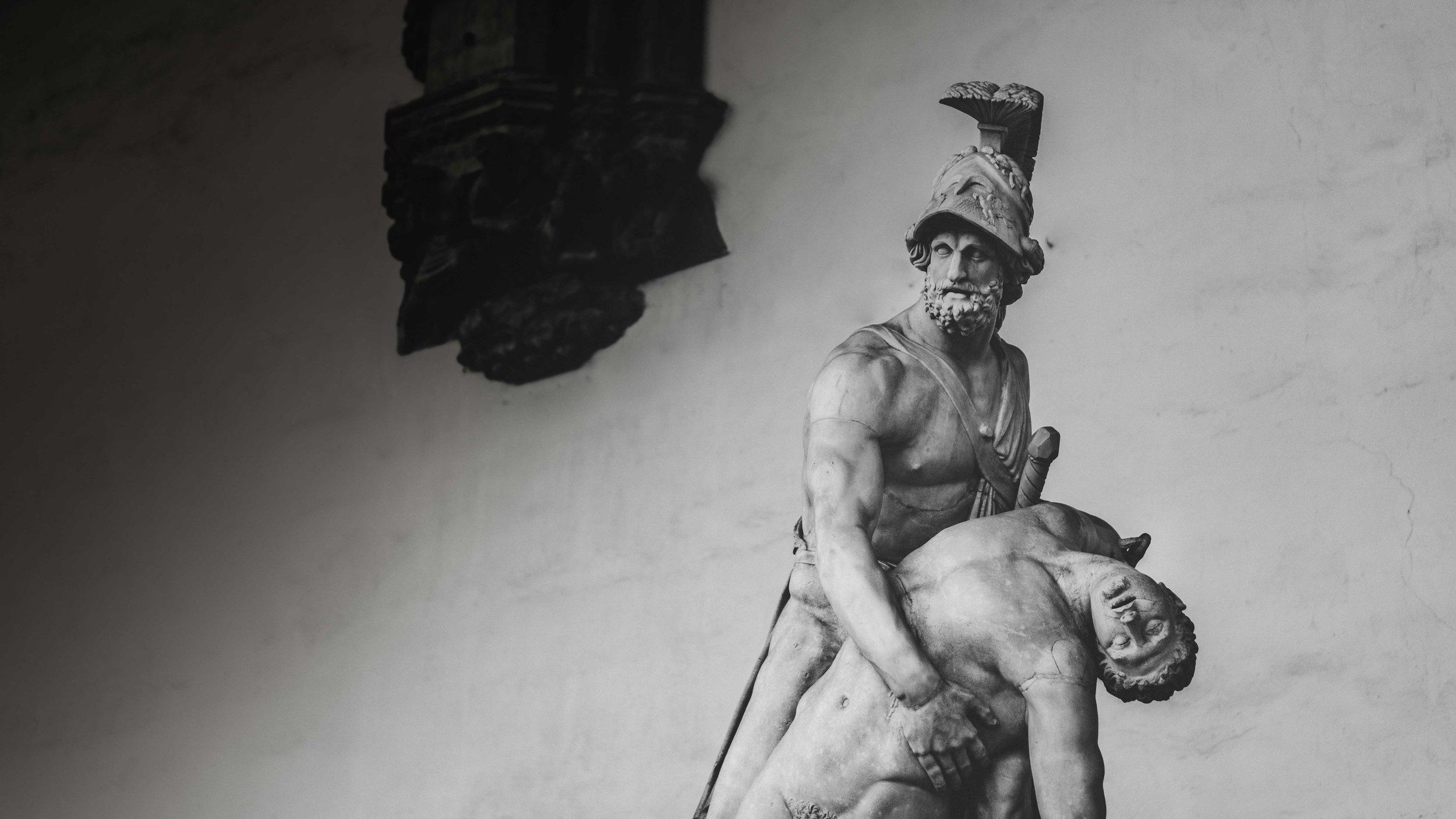 masculine warrior holding a dead man sculpture