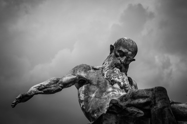 black and white photo of an old man statue with killer clouds in the background