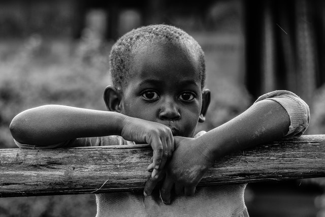 young african boy leaning on a fence