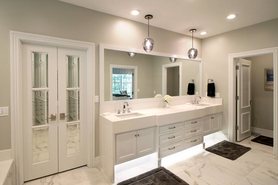 Featuring elevated counters, varied sources of light, functional cabinetry and a white-on-white palette, the master bathroom is a crisp, clean space with a classic, yet contemporary aesthetic.