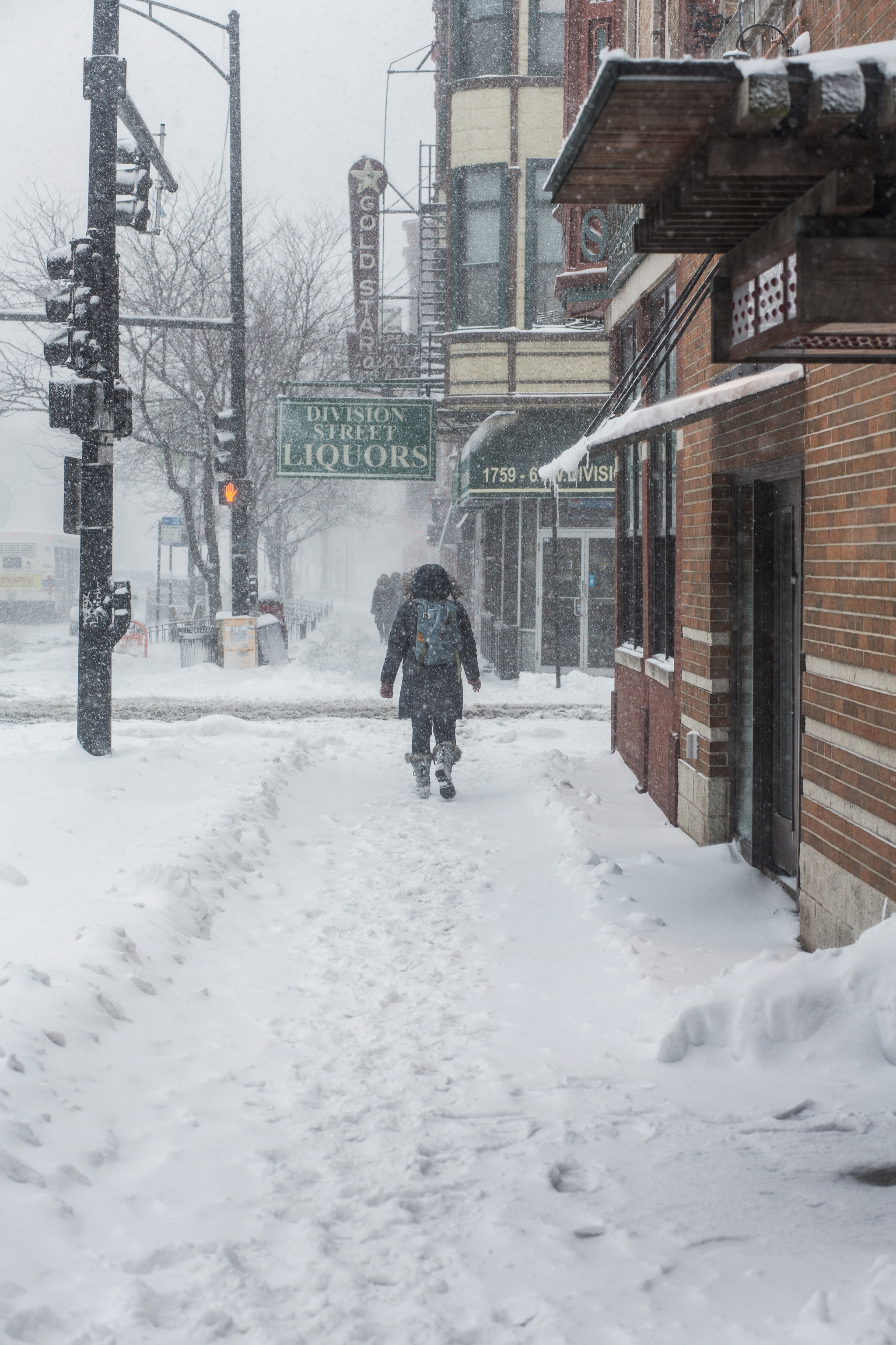 A woman hikes East on W. Division Street during Winter Storm Linus.