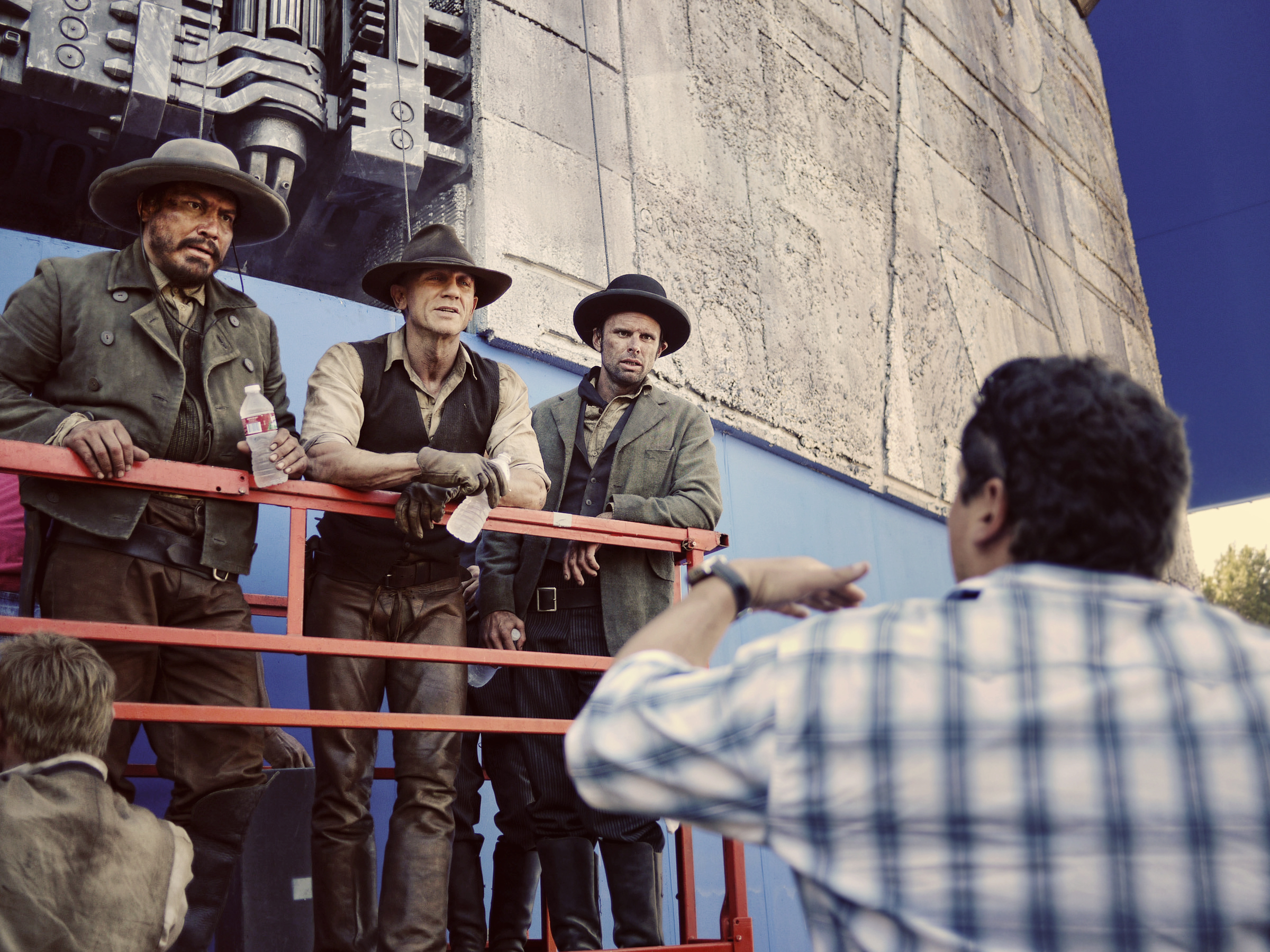 Jon Favreau directs Julio César Cedillo, Daniel Craig and Walton Goggins. They are supported by cables for safety as they will climb the alien ship with the intention of blowing it up.