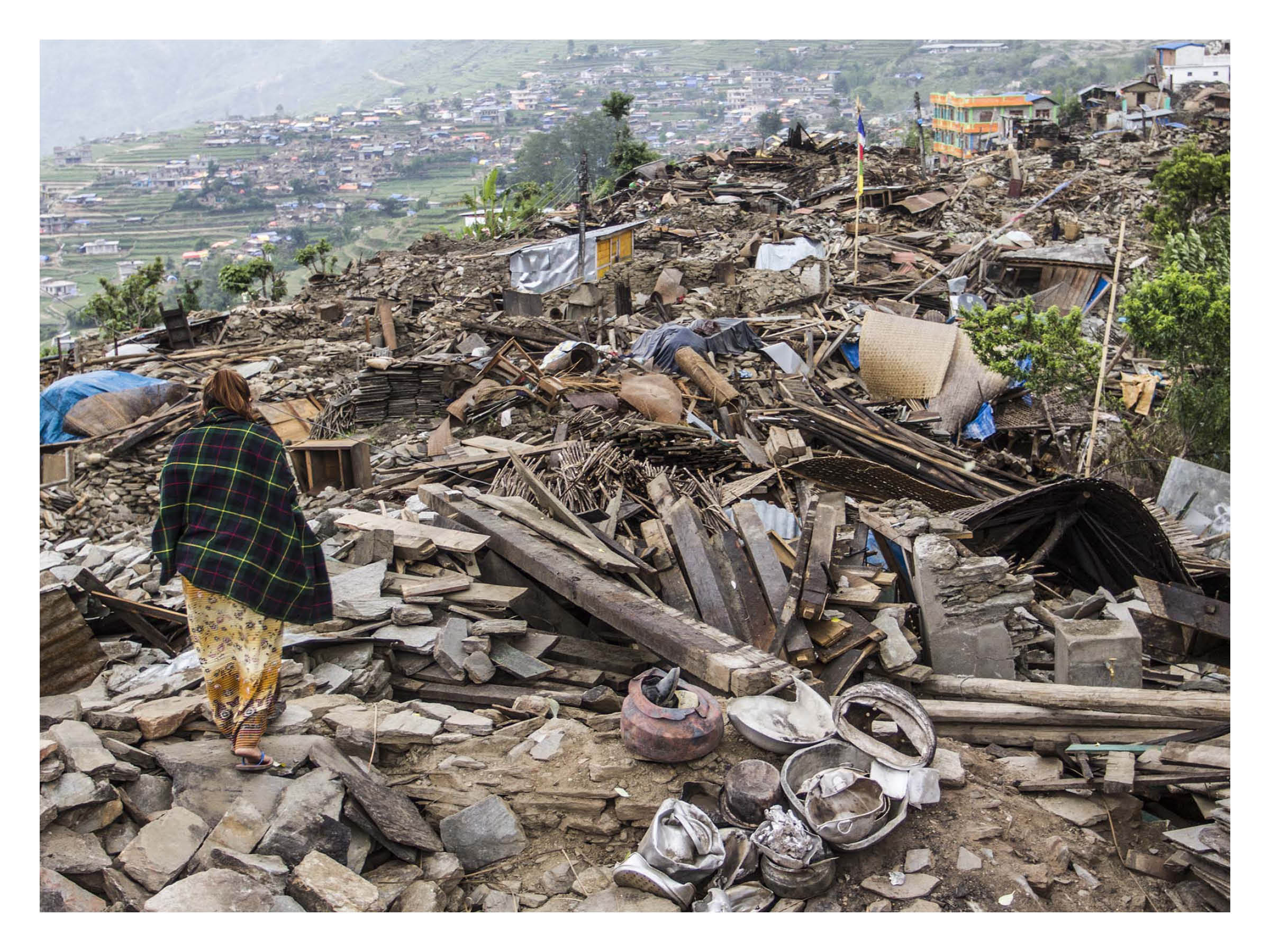 Nepal Earthquake:  At the epicentre of the 2015 #nepal earthquake a woman walks through the remains of the devastated village of Barpak, Gorkha district. The 7.8M earthquake killed an estimated 9000 people on 25th April 2015, followed by another earthquake measuring 7.3M on May 12th with its epicentre on the border of Dolakhaand, Sindhupalchowk district.