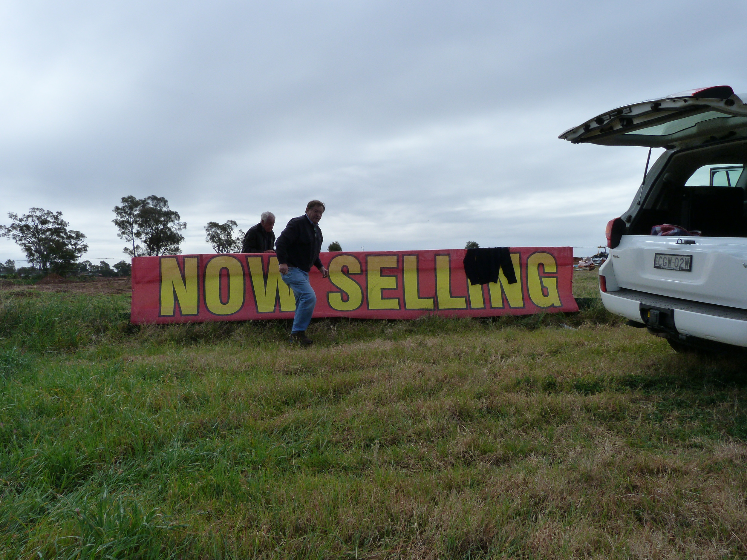 Directors Peter Rogers and John Ireland erectsale banner on Hennessy Drive.